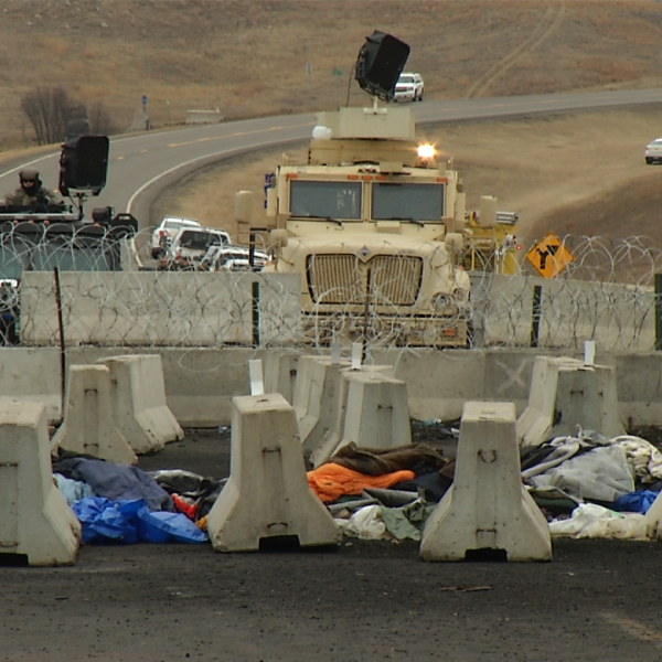Concrete slabs sit in front of several law enforcement vehicles and heavy equipment