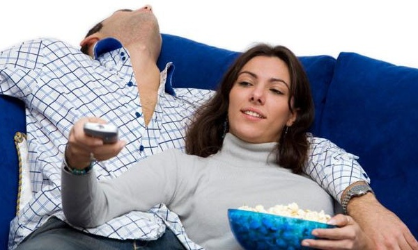 couple on couch with TV remote and popcorn_1798647822218875-159532