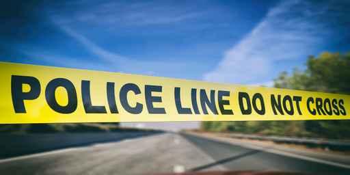 Police line. Warning yellow tape, text do not cross, blur highwa_1556639631575