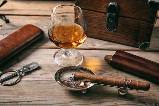 Cuban cigar and a glass of cognac brandy on wooden background_1556031865013