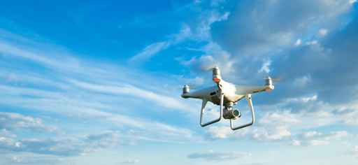 Drone flying overhead in cloudy blue sky_1555344221434